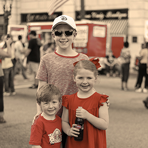 Kids posing at Cheerwine Festival 2018 with bottle of Cheerwine