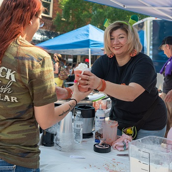 A vendor gives a customer a cheerwine smoothie at the 2019 Cheerwine Festival