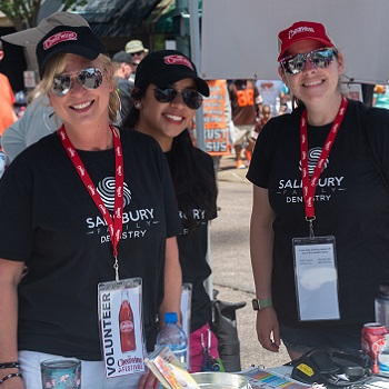 More volunteers pose at a sponsor table at the 2019 Cheerwine Festival