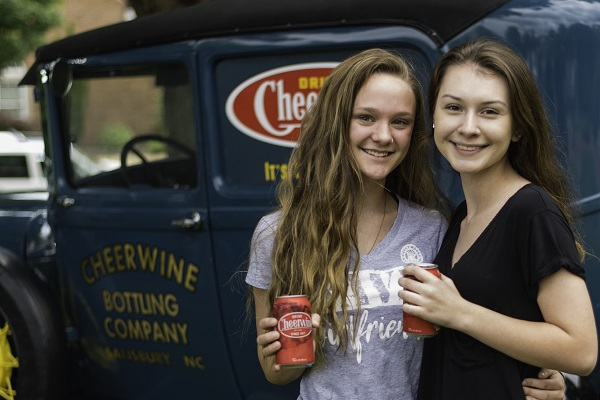 Two girls posing with cheerwine and antique car