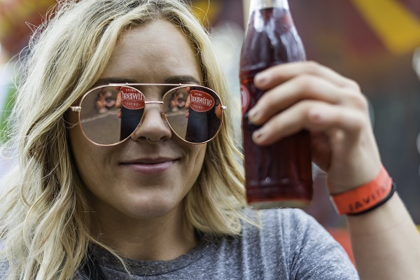 Girl posing with Cheerwine bottle reflected in her sunglasses