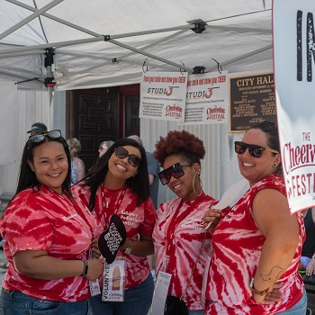 Volunteers pose at a sponsor table at the 2019 CHeerwine Festival